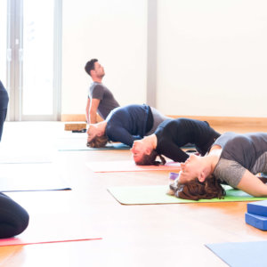 Students holding yoga poses on matts