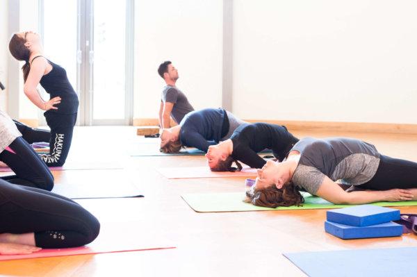 Students holding yoga poses on matts